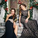 Портрет красивых молодых женщин близнецов в шикарных платьях вечера над предпосылкой рождества Стоковые Изображения RF