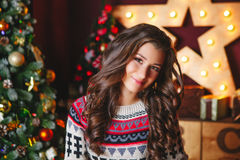 Портрет красивых усмехаясь курчавых женщин приближает к рождественской елке Торжество стоковое изображение