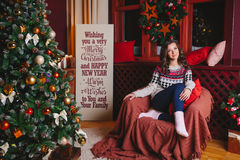 Портрет красивых усмехаясь курчавых женщин приближает к рождественской елке Торжество стоковые фото