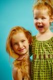 Портрет 2 красных возглавленных маленьких сестер обнимая, выражая теплое отношение стоковое изображение rf