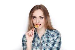 Портрет красоты молодой прелестной свежей смотря белокурой женщины в голубой рубашке шотландки представляя с леденцом на палочке  Стоковые Фотографии RF