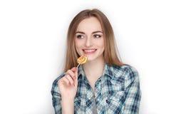 Портрет красоты молодой прелестной свежей смотря белокурой женщины в голубой рубашке шотландки представляя с леденцом на палочке  Стоковое Фото