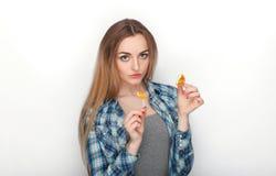 Портрет красоты молодой прелестной свежей смотря белокурой женщины в голубой рубашке шотландки представляя с леденцом на палочке  Стоковая Фотография RF