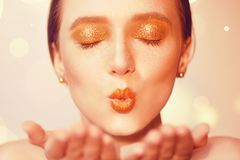Портрет красоты молодой элегантной девушки Красивая женщина брюнет с губами золота и золотым ярким составом, ногтями дуя волшебст Стоковые Изображения RF