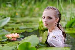 Портрет красоты молодой женщины в воде Девушка с нежным составом в озере среди лотосов и лилий воды напольно Стоковое Изображение
