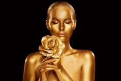 Портрет красоты фотомодели золота с цветком Роза, макияжем золотого искусства женщины роскошным стоковые изображения