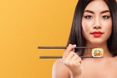 Портрет крупного плана азиатской женщины есть суши и крены на желтой предпосылке Copyspace Стоковое Изображение RF