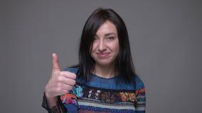 Портрет крупного плана большого пальца руки взрослого кавказского брюнета женского показывая вверх по смотреть камеру с предпосыл видеоматериал