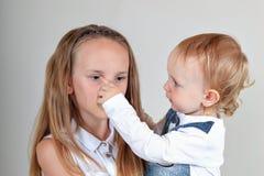 Портрет крупного плана брата и сестры Девушка хмурится, и ребенок пробует развеселить ее вверх Истинные эмоции стоковые изображения rf