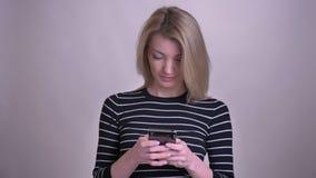 Портрет крупного плана взрослого привлекательного белокурого кавказца женского используя телефон и смотреть камеру усмехаясь с сток-видео