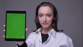 Портрет крупного плана взрослой привлекательной кавказской женщины используя планшет и показывать зеленый экран chroma к камере с акции видеоматериалы