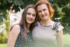 Портрет крупного плана взрослых дочери и матери outdoors Милое брюнет и ее мама смотрят камеру в Стоковые Изображения