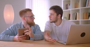 Портрет крупного плана 2 взрослых кавказских бизнесменов используя ноутбук и планшет имея обсуждение внутри помещения в комнате сток-видео