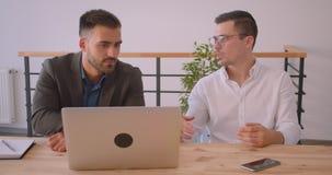 Портрет крупного плана 2 взрослых кавказских бизнесменов обсуждая проект на ноутбуке совместно в офисе внутри помещения акции видеоматериалы