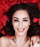 Портрет крупного плана дамы кладя на лепестки розы Стоковое Фото