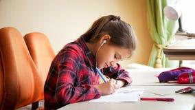 Портрет крупного плана девочка-подростка слушая к музыке делая домашнюю работу в спальне Стоковое Фото