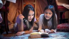 Портрет крупного плана 2 девочка-подростков при электрофонарь лежа на поле и читая страшную книгу стоковое изображение