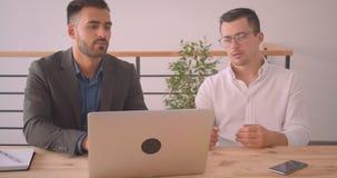 Портрет крупного плана 2 кавказских бизнесменов обсуждая проект на ноутбуке совместно в офисе внутри помещения акции видеоматериалы