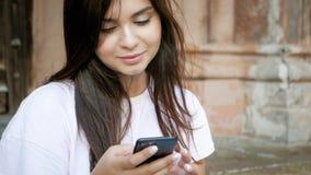 Портрет крупного плана красивой молодой женщины используя мобильный телефон пока сидящ на улице Стоковое фото RF