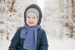 Портрет крупного плана маленькой усмехаясь девушки в снежном лесе зимы Стоковые Изображения