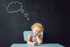 Портрет крупного плана милой маленькой девочки думая глубоко о что-то космос экземпляра Стоковое фото RF