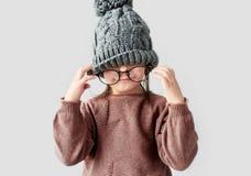 Портрет крупного плана милой смешной маленькой девочки играя в шляпе зимы теплой, нося свитера с круглыми стильными зрелищами на  стоковая фотография