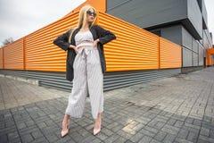 Портрет крупного плана милой усмехаясь маленькой модельной девушки в striped куртке и солнечных очках представляя около серого ри стоковое фото