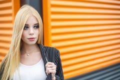 Портрет крупного плана милой усмехаясь маленькой модельной девушки в striped куртке и солнечных очках представляя около серого ри стоковые изображения rf