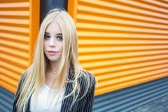 Портрет крупного плана милой усмехаясь маленькой модельной девушки в striped куртке и солнечных очках представляя около серого ри стоковая фотография rf