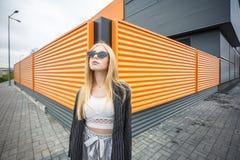 Портрет крупного плана милой усмехаясь маленькой модельной девушки в striped куртке и солнечных очках представляя около серого ри стоковое фото rf