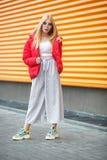 Портрет крупного плана милой усмехаясь маленькой модельной девушки в красной куртке и стеклах представляя около серой рифленой st стоковое изображение rf