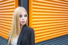 Портрет крупного плана милой усмехаясь маленькой модельной девушки в striped куртке и солнечных очках представляя около серого ри стоковые фотографии rf