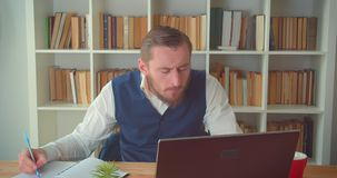 Портрет крупного плана молодого кавказского бизнесмена используя ноутбук и принимающ примечания в офис внутри помещения с книжным сток-видео