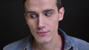 Портрет крупного плана молодого кавказского человека жмурясь его глаза делая смешное выражение лица сток-видео