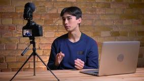 Портрет крупного плана молодого корейского мужского блоггера говоря на камере быть привоженный в ярость и жалуясь внутри помещени акции видеоматериалы