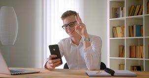 Портрет крупного плана молодого красивого кавказского бизнесмена в стеклах принимая selfies по телефону усмехаясь жизнерадостно акции видеоматериалы