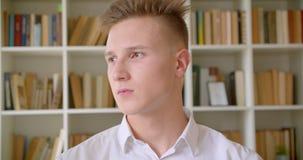 Портрет крупного плана молодого красивого кавказского студента усмехаясь счастливо смотрящ камеру в библиотеке колледжа внутри по акции видеоматериалы