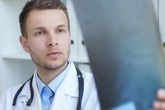 Портрет крупного плана молодого красивого мужского доктора смотря рентгеновский снимок Стоковое Изображение