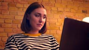 Портрет крупного плана молодого милого девочка-подростка используя ноутбук и смеющся жизнерадостно сидеть на кресле в уютном акции видеоматериалы