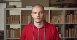 Портрет крупного плана молодого привлекательного кавказского студента кивая говорящ да показывать согласование смотря камеру внут акции видеоматериалы