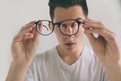 Портрет крупного плана молодого человека с стеклами Он имеет проблемы зрения и жмурится его глаза немного красиво стоковые изображения rf