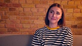 Портрет крупного плана молодой жизнерадостной женщины смотря комедию по телевизору смеяться счастливо сидеть на софе будучи ослаб видеоматериал