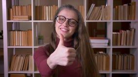 Портрет крупного плана молодой кавказской студентки в стеклах показывая большой палец руки вверх по усмехаться счастливо смотря к акции видеоматериалы