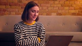Портрет крупного плана молодой милой девушки имея видео- звонок на ноутбуке усмехаясь и смеясь счастливо сидеть на акции видеоматериалы