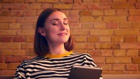 Портрет крупного плана молодой милой девушки имея видео- звонок на планшете и говоря жизнерадостно усмехаясь усаживание на акции видеоматериалы
