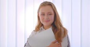 Портрет крупного плана молодой милой кавказской девушки держа ноутбук смотря камеру усмехаясь счастливо стоящ внутри помещения в видеоматериал