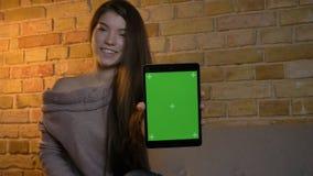 Портрет крупного плана молодой милой кавказской женщины используя промежуток времени и показывать планшета зеленому chroma ключев стоковые фотографии rf