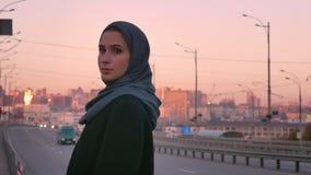 Портрет крупного плана молодых привлекательных мусульман в hijab смотря камеру и представляя готовящ проходя автомобили с видеоматериал