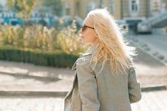 Портрет крупного плана на открытом воздухе молодой усмехаясь белокурой женщины с солнечными очками с длинным вьющиеся волосы На д стоковое изображение