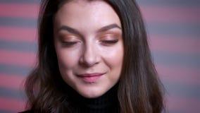 Портрет крупного плана очаровывать молодую кавказскую женщину смотря камеру и исправляя ее волосы акции видеоматериалы